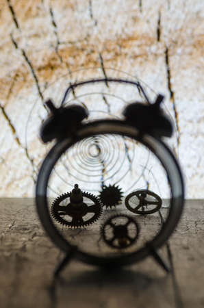 Broken alarm clock with the gears on the background of wood rings. Close up. 스톡 콘텐츠