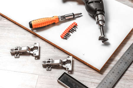 The tool is a drill and a square prepared for marking and inset furniture hinges. Banque d'images