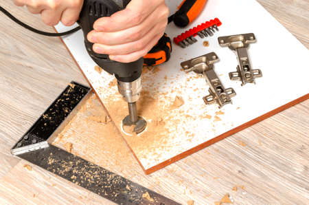 Man drills holes for installation of furniture hinges for facade of kitchen.