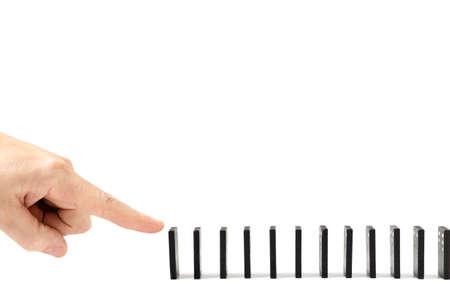 Finger, menschliche Hand lässt die Knochen von Dominosteinen auf weißem Hintergrund fallen. Standard-Bild