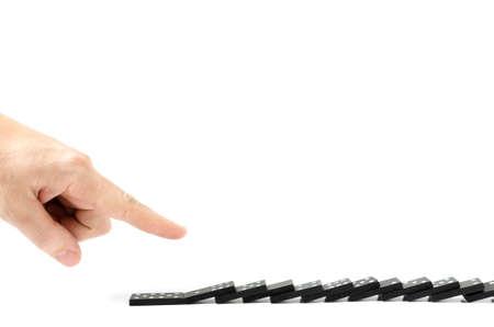 Finger, menschliche Hand lässt die Knochen von Dominosteinen auf weißem Hintergrund fallen.