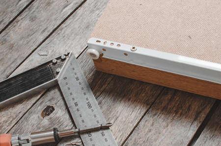 Schroevendraaier metalen meethoek en gemonteerde meubeldoos met geschroefde geleidingen.