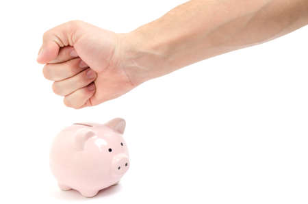 Male fist wants to smash pink piggy Bank on white background.