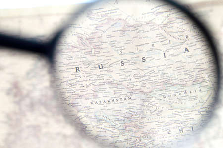 Old map with territory of Russia and name of country is enlarged through a magnifying glass.