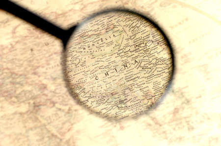Old map with territory of China and name of country is enlarged through a magnifying glass. Imagens