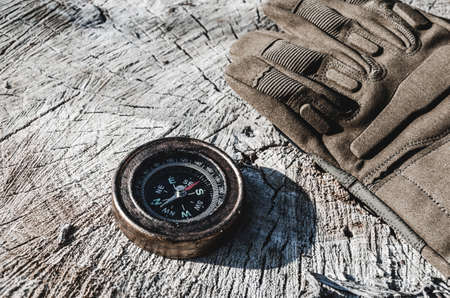 An old compass and military gloves on the stump of a cut tree. Stockfoto