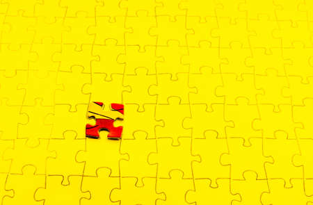 Assembled puzzle on a yellow background, highlight one of the red cells of the puzzle. Reklamní fotografie