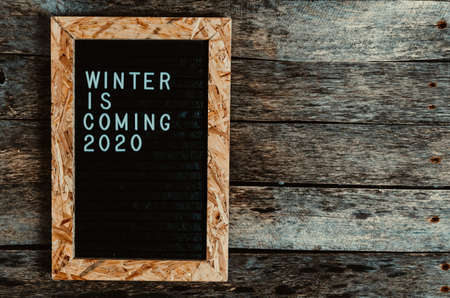 Letter board with white lettering winter is coming on old wooden background. Фото со стока