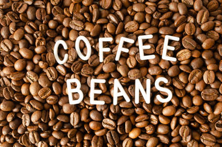 Background with coffee beans with white inscription in the middle.