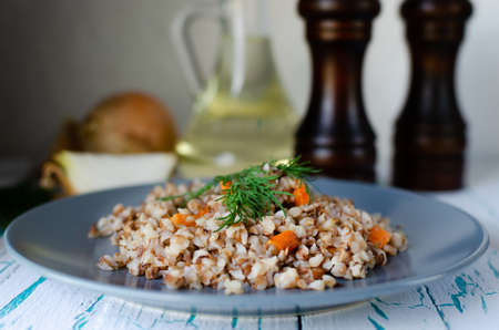 Buckwheat porridge with carrots and dill in a blue plate. On background of Golden onions, green dill and salt and pepper mills. 스톡 콘텐츠