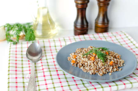 Buckwheat porridge with carrots and dill in a gray plate. In the background, green dill and salt and pepper mills. 스톡 콘텐츠