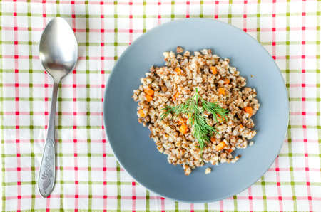Buckwheat porridge in a gray plate on a background of a checkered napkin. Healthy food.