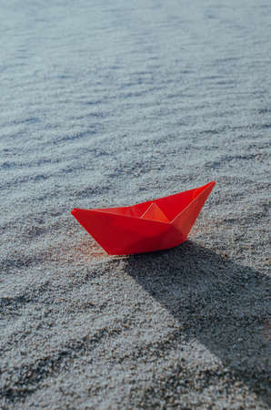 Red paper boat at the bottom of a dry sea. Beach, heat and vacation.Ecology, drought.
