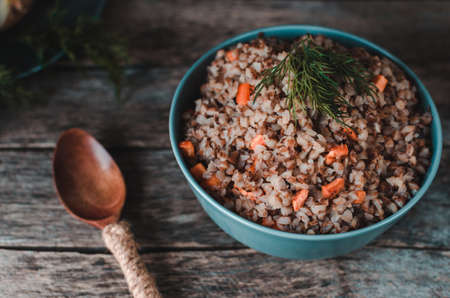 Buckwheat porridge with carrots on an old rustic, wooden background. Cutlery, oil bottle, dill, pepper and salt shaker, onion.