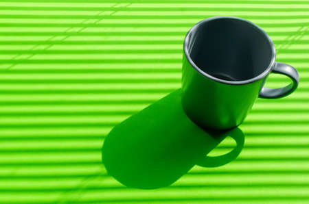 Grey mug on a green background with hard shadows from the rays of the bright sun making its way through the blinds.