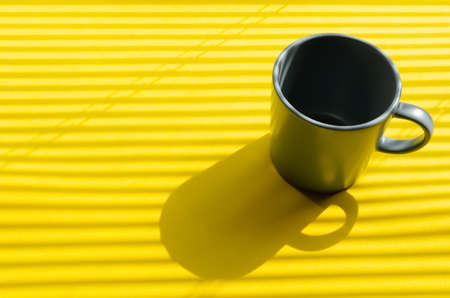 Grey mug on a yellow background with hard shadows from the rays of the bright sun making its way through the blinds.