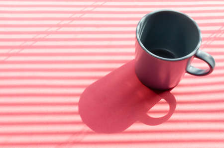 Grey mug on a pink background with hard shadows from the rays of the bright sun making its way through the blinds. Reklamní fotografie