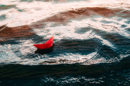 Un petit bateau en papier rouge fait naufrage dans une mer agitée et déchaînée.