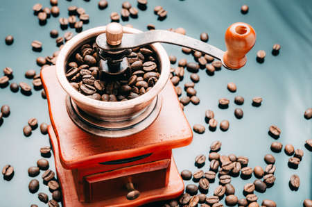 Coffee grinder with coffee beans on the reflective surface. Making coffee. 스톡 콘텐츠