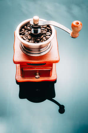 Coffee grinder with coffee beans on the reflective surface. Making coffee. Reklamní fotografie