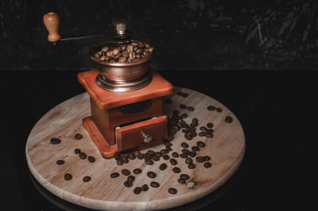 Old wooden coffee grinder and coffee beans on concrete background.
