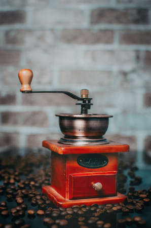 Old wooden coffee grinder and coffee beans.