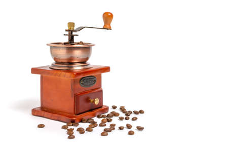 Retro wooden coffee grinder on white background with coffee beans.