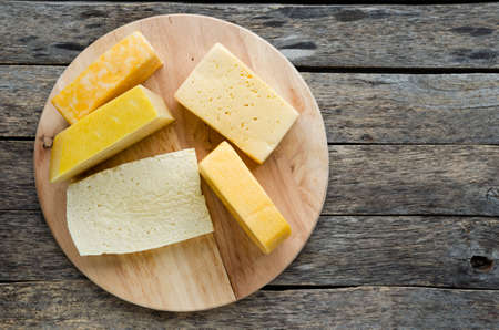 Wide variety of cheese on an old, rustic wooden table.