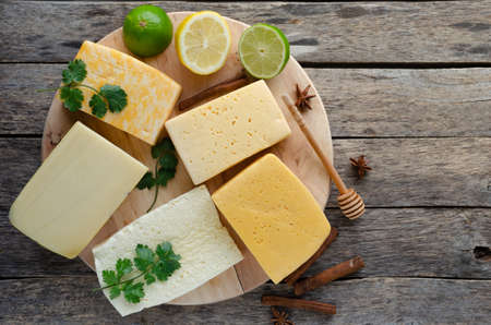 Large variety of cheese with lemon and lime laid on a round cutting Board, also parsley, spices and a spoon of honey on rustikalnom the table