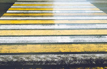 Slippery road with a pedestrian crossing painted in yellow and white Zebra with glare after rain.
