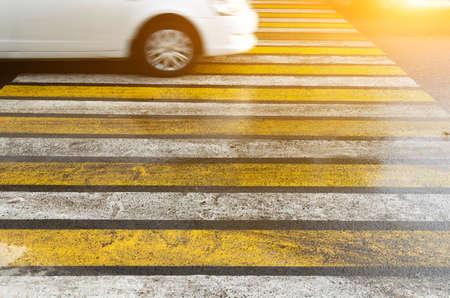 Das Auto passiert mit hoher Geschwindigkeit einen im Regen rutschigen Fußgängerüberweg. Standard-Bild
