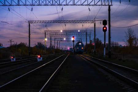 Train moves on tracks in evening.Railway transportation, passenger train.