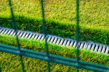 Drainage system on the football field with a bright green lawn.