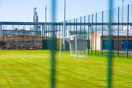 Football field with a bright green lawn, on the background of a steel plant. Stok Fotoğraf