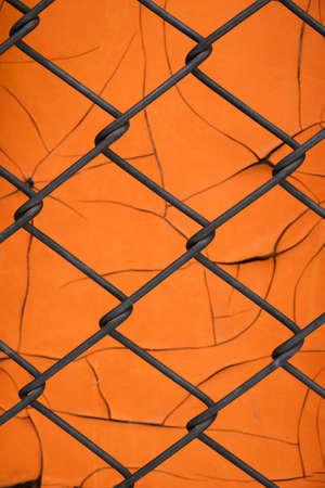 Orange background of old peeling paint and mesh netting.