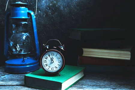 An old vintage alarm clock on a table among books and a kerosene lamp in the moonlight.