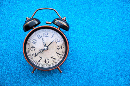 Old, vintage retro alarm clock on a bright blue background