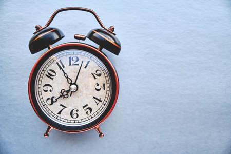 Old, vintage retro alarm clock on a gray background