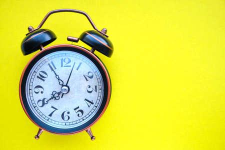 Old, vintage retro alarm clock on a bright yellow background Banco de Imagens
