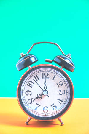 Vintage old alarm clock on a background of pastel retro colors