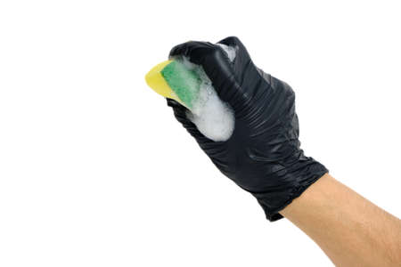 Man hand in a black glove clutches a foam sponge for washing dishes with foam