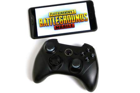 Kostanay, Kazakhstan, February 12, 2020.Joystick and mobile phone with the logo of the popular game Playerunknowns Battlegrounds abbreviated PUBG on white background.
