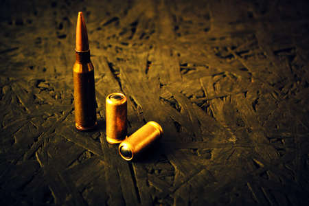 Bullets from a machine gun and a pistol on a dark background