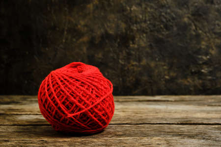 Red ball of wool yarn against an old wall
