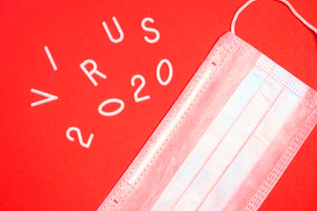 Medical mask for protection and the inscription virus 2020 on a red background
