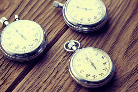 Three retro mechanical stopwatches on a wooden background