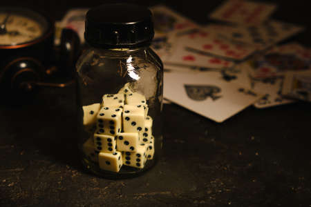 Bottle with dice on table in an underground casino on background of card and an abandoned alarm clock