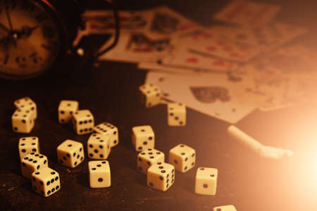 Dice,cigarettes, cards, and an abandoned alarm clock on a table in an underground casino