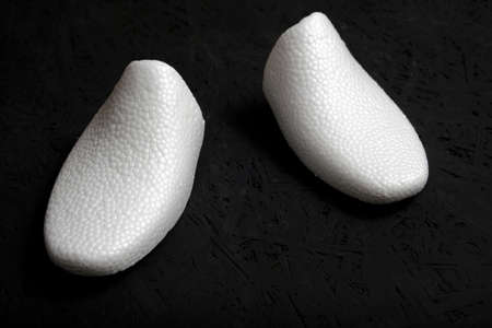 Shoe form made of white foam on a black background