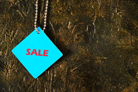 Blue tag with the words sale on a concrete background
